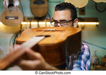 El fabricante de lute revisa el puente y el brazo de la guitarra clásica