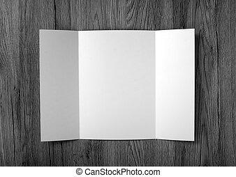 El folleto de la puerta en blanco sobre antecedentes de madera para reemplazar tu diseño.