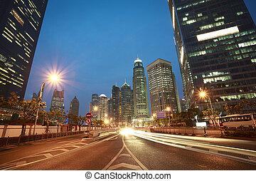 El fondo urbano de los edificios modernos de oficinas, los caminos nocturnos en Shangai