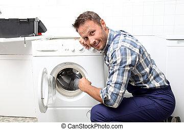 El fontanero está arreglando la lavadora rota