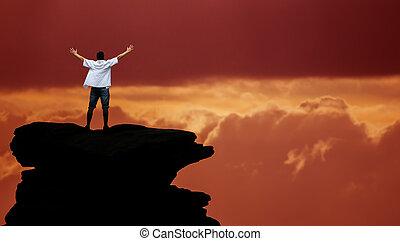 El ganador parado en la cima de la montaña sobre el dramático cielo
