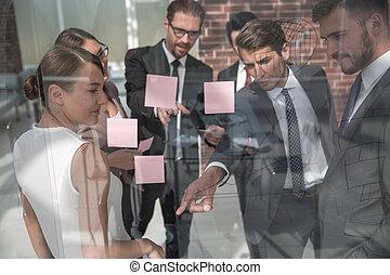 El gerente muestra notas de negocios del equipo