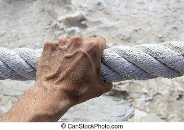 El hombre agarra fuerte cuerda de gran edad
