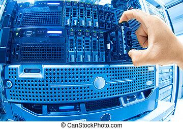 El hombre arregla la red de servidores en el centro de datos