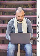 El hombre con la computadora portátil al aire libre