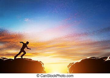 El hombre corre rápido para saltar sobre el precipicio entre dos montañas. Desafío