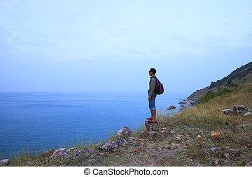 El hombre de la mochila parado en la montaña de roca y buscando el uso del océano para la escena natural multipropósito