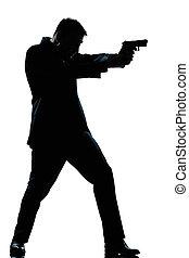 El hombre de la silueta disparando con un arma