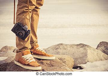 El hombre de los pies y la cámara retro de fotos clásica al aire libre concepto de vacaciones al estilo de vida al aire libre