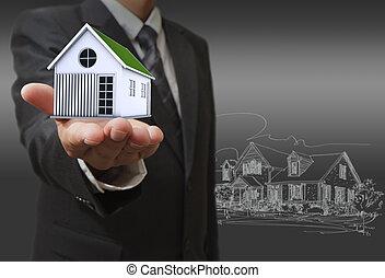 El hombre de negocios muestra una casa