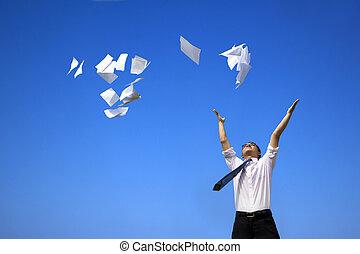 El hombre de negocios se relaja y arroja papeles blancos al cielo azul