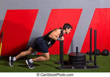 El hombre del trineo empujando pesas haciendo ejercicio