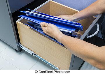 El hombre entrega documentos de archivos de búsqueda en un archivador. Retención