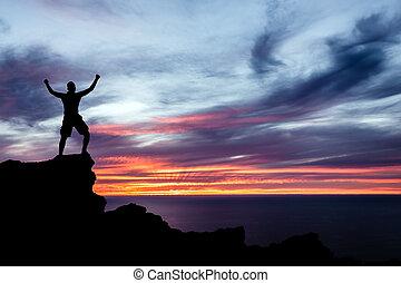 El hombre escalando silueta en montañas, océano y atardecer