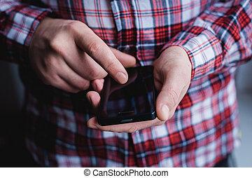 El hombre está usando un smartphone. Teléfono móvil moderno en la mano.