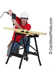 El hombre perforando madera