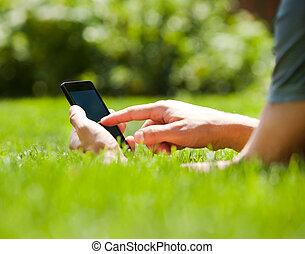 El hombre que usa teléfono móvil inteligente al aire libre en verano