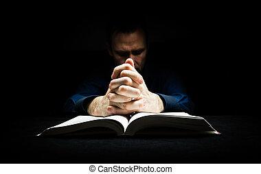 El hombre rezando a Dios con sus manos descansando en una Biblia.