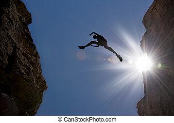 El hombre salta a través de la brecha en la montaña