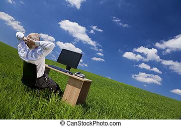 El hombre se relaja en la oficina en un campo verde