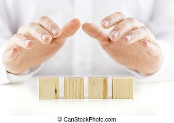 El hombre sosteniendo sus manos sobre una fila de cuatro cubos de madera en blanco en una mesa reflectante en una imagen conceptual. Listo para tu mensaje.