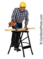 El hombre suavizando la tabla de madera con Sander