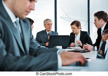 El informe de negocios de la laptop en la reunión de la oficina