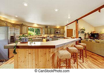 El interior de la cocina brillante con una gran barra de madera y una nevera de acero inoxidable.