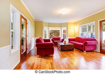 El interior del salón con sofás rojos en la granja de caballos