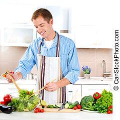 El joven cocinando. Comida sana. Ensalada vegetal