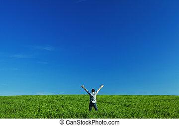 El joven estiró los brazos en verde campo contra el cielo azul