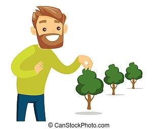 El joven jardinero blanco caucásico planta un árbol.