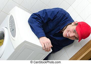 El joven trabajador que repara la lavadora