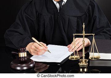 El juez está escribiendo en el escritorio