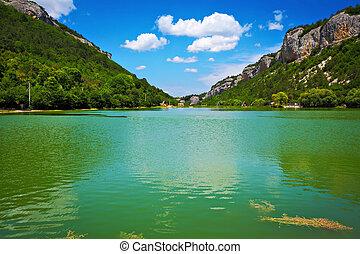 El lago y el cielo azul con nubes entre las montañas