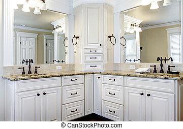 El lujo de los grandes armarios de baños blancos con dobles lavabos.