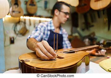 El luteador artesano afinando guitarra clásica a mano con diapason