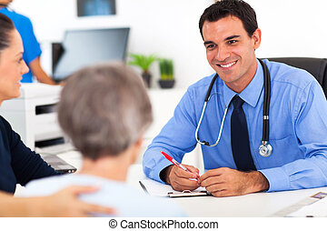 El médico consulta a un paciente mayor