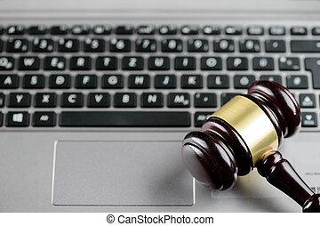 El martillo de madera en un teclado de computadora. Derecho cibernético y crimen