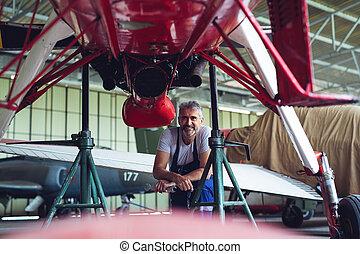 El mecánico de mantenimiento de aviones inspeccionando y trabajando
