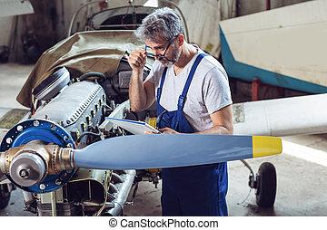El mecánico de mantenimiento inspecciona el motor del avión
