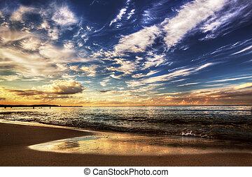 El océano tranquilo bajo el dramático cielo del atardecer