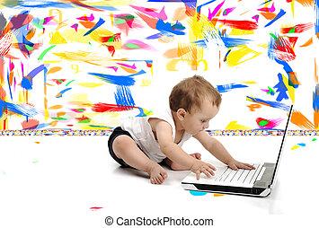 El pequeño niño está sentado en el piso con su portátil, aislado sobre la pared blanca, en un cuarto pintado de desorden con muchos colores alrededor