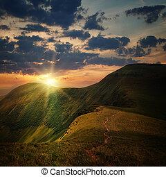 El pico de la colina con sendero y el atardecer de la montaña