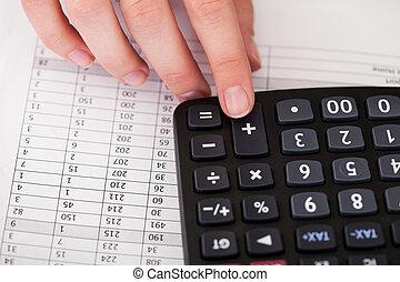 El primer plano de la mano con la calculadora