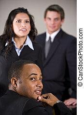 El primer plano de tres ejecutivos multirraciales en una reunión