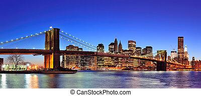 El puente de Brooklyn con la ciudad de Nueva York, Manhattan, en el centro del centro, un panorama al atardecer iluminado sobre East River con un cielo azul claro.