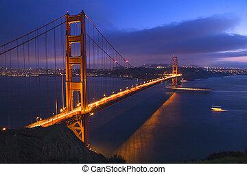 El puente de Golden Gate de noche con los barcos San Francisco California