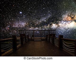 El puente de madera, cielo oscuro, camino lechoso por la noche