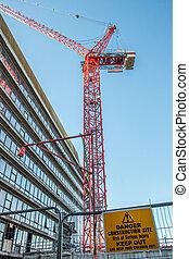 El sitio de construcción de peligros mantiene fuera la señal con la grúa roja sobre el edificio de la oficina de la ciudad